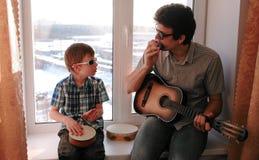 弹奏在太阳镜的一个乐器 爸爸弹吉他,并且儿子演奏坐在窗台的鼓 图库摄影