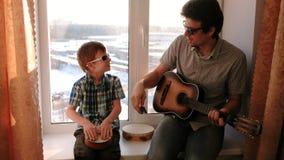 弹奏在太阳镜的一个乐器 爸爸弹吉他,并且儿子演奏坐在窗台的鼓 股票录像