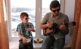 弹奏在太阳镜的一个乐器 爸爸弹吉他,并且儿子演奏坐在窗台的鼓 免版税库存照片