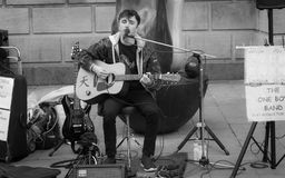 弹奏多台仪器和唱歌在剑桥街道的一个十几岁的男孩  图库摄影
