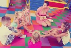 弹奏音乐家仪器的孩子听的老师 库存照片