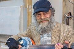 弹奏仪器的老街道上的人 免版税库存图片
