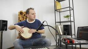 弹奏djembe鼓仪器的音乐家在家庭音乐演播室 股票录像