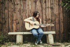 弹她的吉他的美丽的女孩 免版税图库摄影