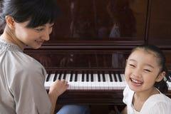 弹她的女儿的母亲钢琴 库存照片