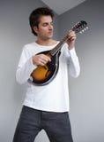 弹小吉他的音乐家 免版税库存图片