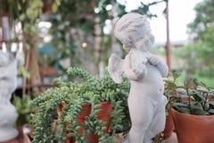 弹小提琴和凝视在一个绿色庭院里的一个逗人喜爱的白色丘比特雕塑有被弄脏的自然背景和bokeh光 免版税库存照片