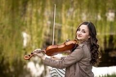 弹小提琴的时兴的年轻女人在公园 库存图片