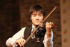 弹小提琴的男孩 免版税库存照片