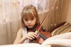 弹小提琴的白肤金发的青春期前的女孩 免版税库存照片