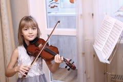 弹小提琴的白肤金发的青春期前的女孩 免版税图库摄影