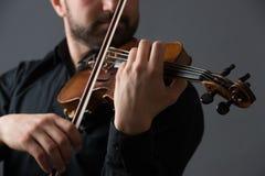 弹小提琴的音乐家人 在执行者的乐器 库存图片