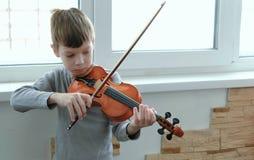 弹小提琴 七岁弹小提琴的男孩在窗口附近 正面图 库存照片