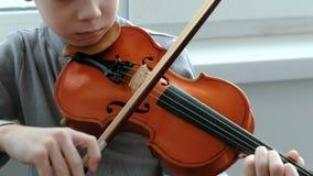 弹小提琴 无法认出的七岁播放小提琴特写镜头的男孩 正面图 影视素材