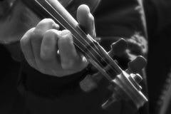 弹小提琴的一个人的手 免版税图库摄影