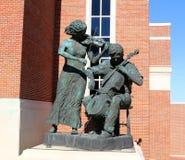 弹小提琴的男人和妇女的雕象在好极了小姐校园里的格特鲁德Castellow福特中心  免版税库存照片