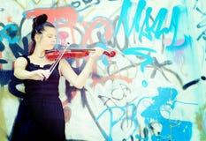 弹小提琴的美丽的少妇 免版税库存照片