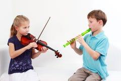 弹小提琴的长笛孩子 图库摄影