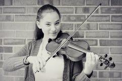 弹小提琴的青少年的女孩 库存图片