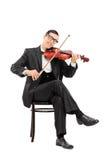 弹小提琴的年轻小提琴手供以座位在椅子 免版税库存照片