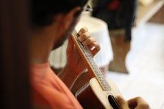 弹尤克里里琴吉他的音乐家 免版税图库摄影