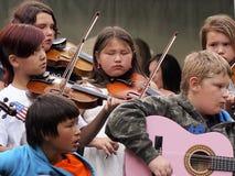 弹无意识而不停地拨弄和吉他的孩子 免版税库存图片