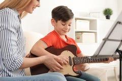 弹有他的老师的小男孩吉他在音乐课 库存照片