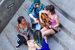 弹有她的朋友的妇女吉他 免版税库存图片