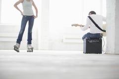 弹有妇女的人电吉他佩带在W的轴向冰鞋 免版税图库摄影