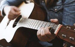 弹有牛仔裤衬衣的女孩声学吉他 库存照片