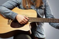 弹有牛仔裤衬衣的女孩声学吉他 免版税库存照片