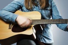 弹有牛仔裤衬衣的女孩声学吉他 库存图片