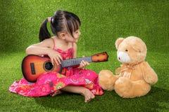 弹有玩具熊的亚裔矮小的中国女孩吉他 图库摄影