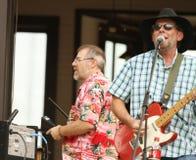 弹母牛响铃和电吉他的两个人在一个室外音乐会期间 免版税库存图片