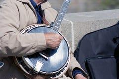 弹班卓琵琶的人的手 免版税图库摄影