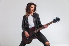 弹电吉他的一个凉快的妇女吉他弹奏者的侧视图 免版税图库摄影