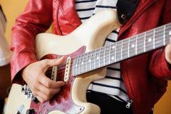 弹电吉他的妇女的中央部位 免版税库存照片