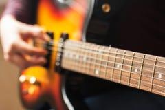 弹电吉他的妇女的手 免版税库存图片