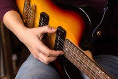 弹电吉他的妇女的手 免版税库存照片