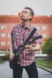 弹电吉他的短的袖子衬衣的人 免版税库存照片