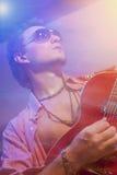 弹电吉他的英俊的吉他弹奏者 射击与闪光灯 免版税库存图片