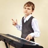 弹电子钢琴的衣服的小钢琴演奏家 免版税库存照片