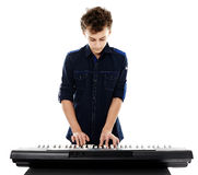 弹电子钢琴的少年 免版税库存照片