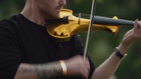 弹电小提琴的慢动作年轻热情的音乐家人在城市公园 股票视频