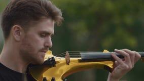 弹电小提琴的年轻热情的音乐家人在城市公园 股票视频