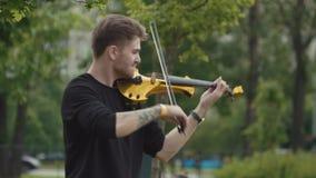 弹电小提琴的年轻热情的音乐家人在城市公园 股票录像