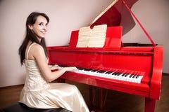 弹红色大平台钢琴的妇女 免版税库存照片