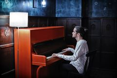 弹红色钢琴的年轻有胡子的人 免版税库存照片