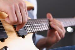 弹经典形状电吉他的男性胳膊 图库摄影