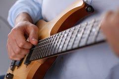 弹经典形状电吉他的男性胳膊 库存照片